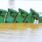 schiefe Mülltonnen im Wasser